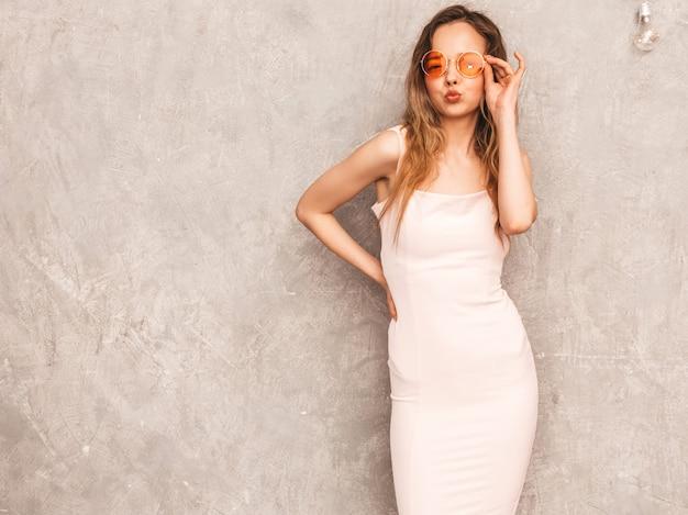 Ritratto di giovane bella ragazza sorridente in abito rosa chiaro estivo alla moda. posa sexy donna spensierata. modello positivo divertendosi in occhiali da sole rotondi Foto Gratuite