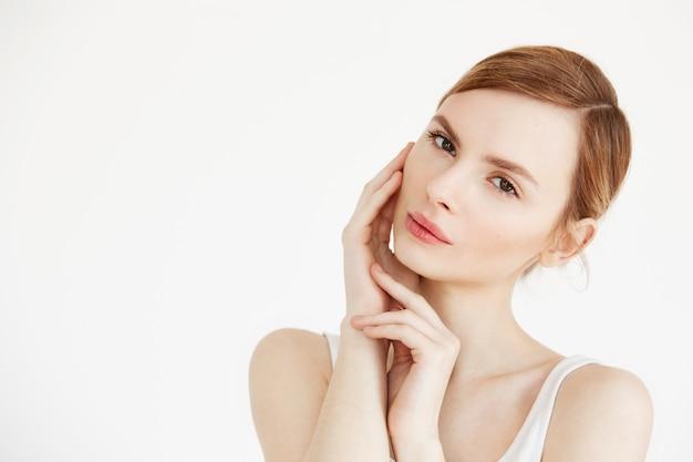 Ritratto di giovane bella ragazza toccando il viso. trattamento facciale. cosmetologia di bellezza e cura della pelle. Foto Gratuite