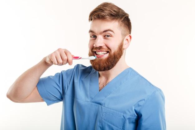 Ritratto di giovane dentista insegnando al paziente come lavarsi i denti Foto Gratuite