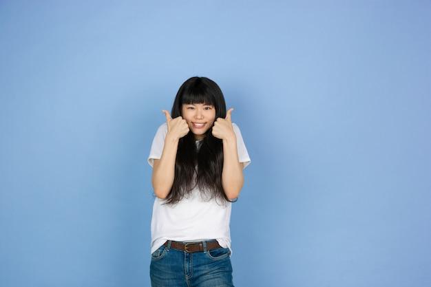 Ritratto di giovane donna asiatica isolata sullo spazio blu dello studio Foto Gratuite