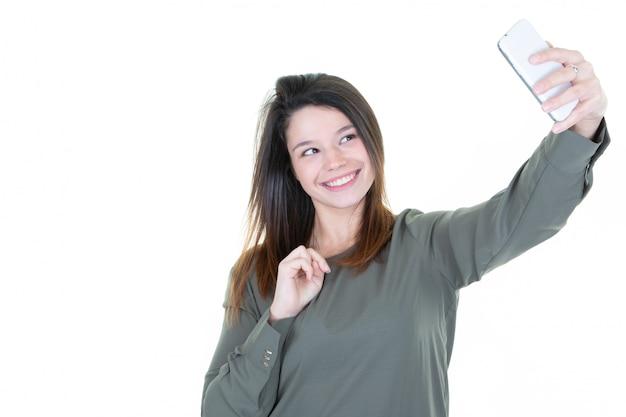 Ritratto di giovane donna attraente che fa la foto del selfie con lo smartphone su fondo bianco Foto Premium