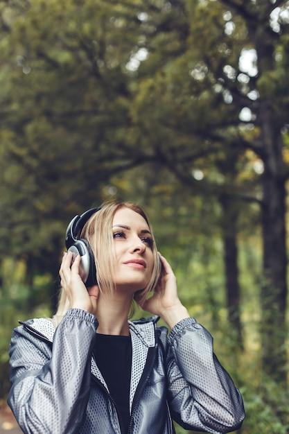 Ritratto di giovane donna attraente su un parco cittadino, ascoltando musica in cuffia Foto Premium