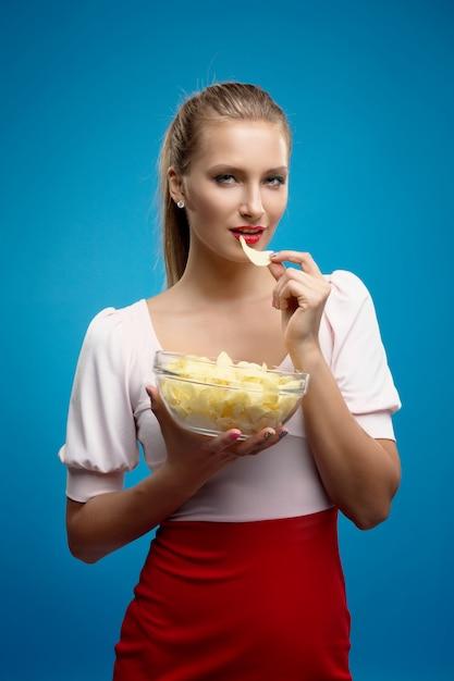 Ritratto di giovane donna bionda alla moda in abito rosa-rosso, belle labbra, trucco luminoso holding, mangiare patate fritte, patatine fritte, patatine e in posa sul muro blu. Foto Premium