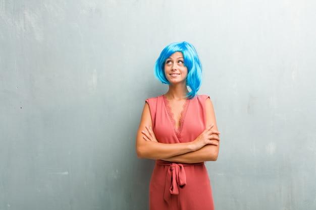Ritratto di giovane donna bionda elegante guardando in alto, pensando a qualcosa di divertente e avendo un Foto Premium