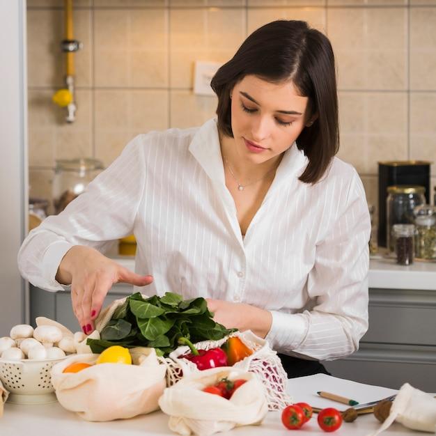 Ritratto di giovane donna che controlla generi alimentari Foto Gratuite