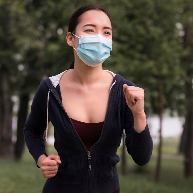Ritratto di giovane donna che funziona con la mascherina chirurgica Foto Gratuite