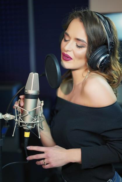 Ritratto di giovane donna che registra una canzone in uno studio professionale. Foto Premium