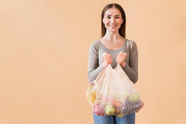 Ritratto di giovane donna con borsa riutilizzabile con generi alimentari Foto Gratuite