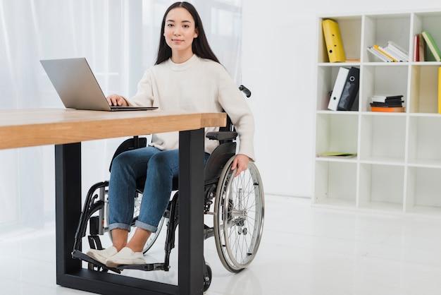 Ritratto di giovane donna di affari sicura che si siede sulla sedia a rotelle che utilizza computer portatile nell'ufficio Foto Gratuite