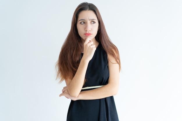 Ritratto di giovane donna dubbiosa in piedi con la mano sul mento Foto Gratuite