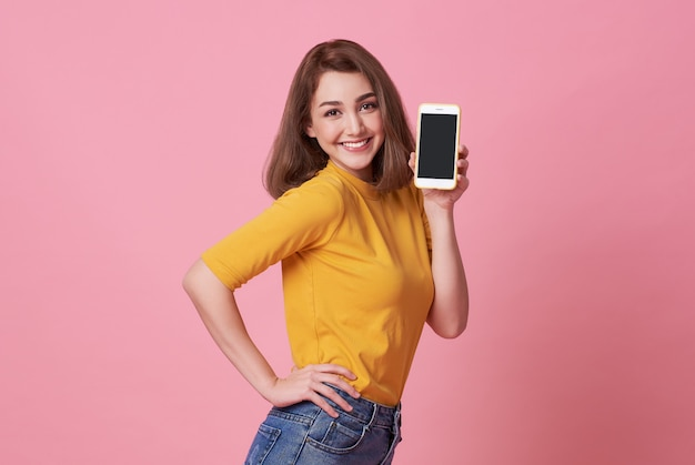 Ritratto di giovane donna felice che mostra al telefono cellulare schermo vuoto isolato su rosa. Foto Premium