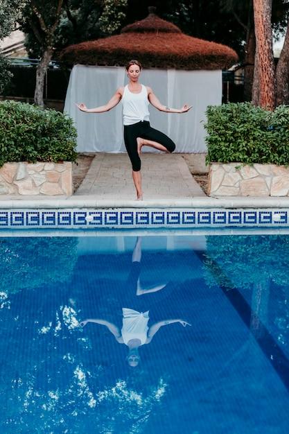 Ritratto di giovane donna (fitness, yoga, corpo sano) in piscina Foto Premium