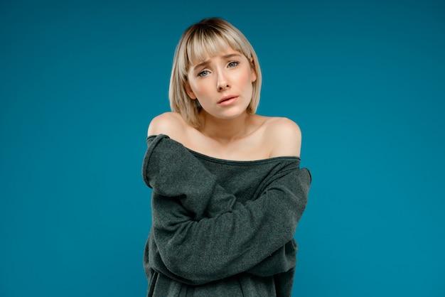 Ritratto di giovane donna graziosa bionda sopra la parete blu Foto Gratuite