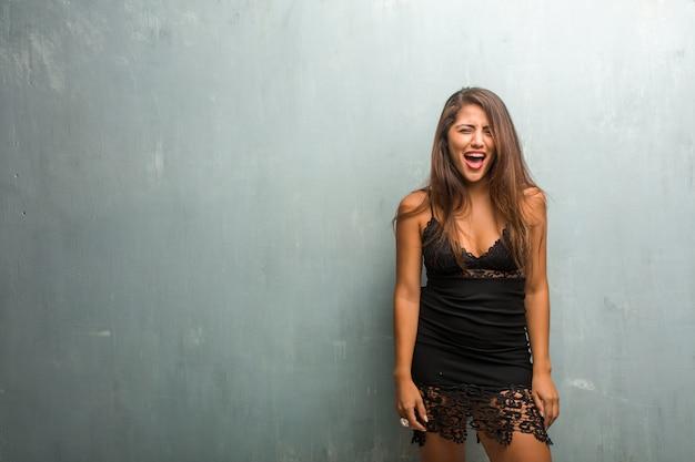 Ritratto di giovane donna graziosa che indossa un abito contro un muro molto arrabbiato e sconvolto Foto Premium