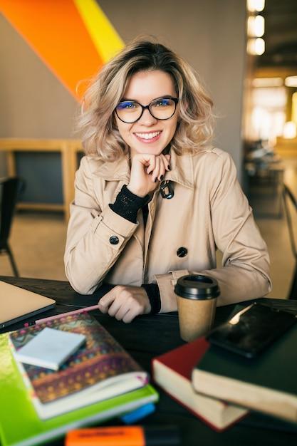 Ritratto di giovane donna graziosa che si siede al tavolo in trench lavorando sul portatile in ufficio di co-working, con gli occhiali, sorridente, felice, positivo, sul posto di lavoro Foto Gratuite