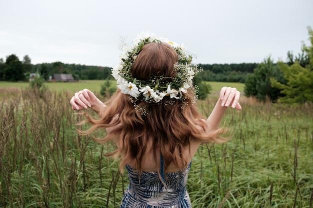 Ritratto di giovane donna graziosa con cerchietto di fiori di camomilla sulla testa Foto Premium