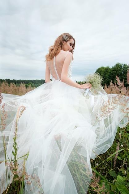 Ritratto di giovane donna graziosa in abito da sposa bianco all'aperto Foto Premium