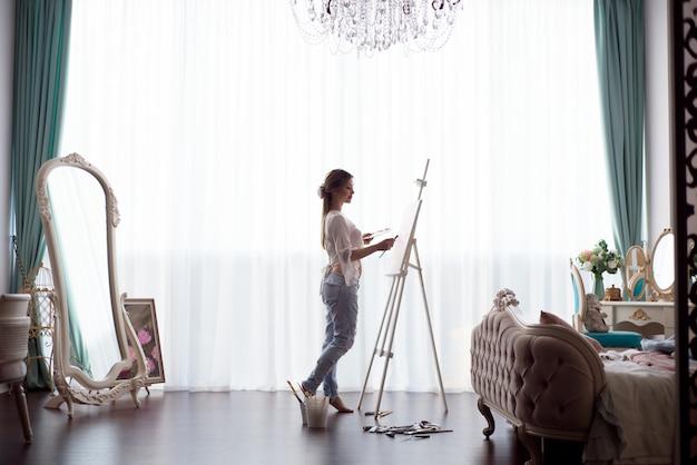 Ritratto di giovane donna pragnant che dipinge con le pitture ad olio su tela bianca, ritratto di vista laterale Foto Premium