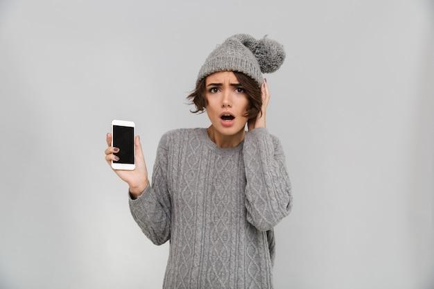 Ritratto di giovane donna scioccata in maglione e cappello Foto Gratuite