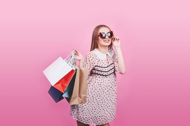 Ritratto di giovane donna sorridente felice con i sacchetti della spesa sul rosa Foto Premium