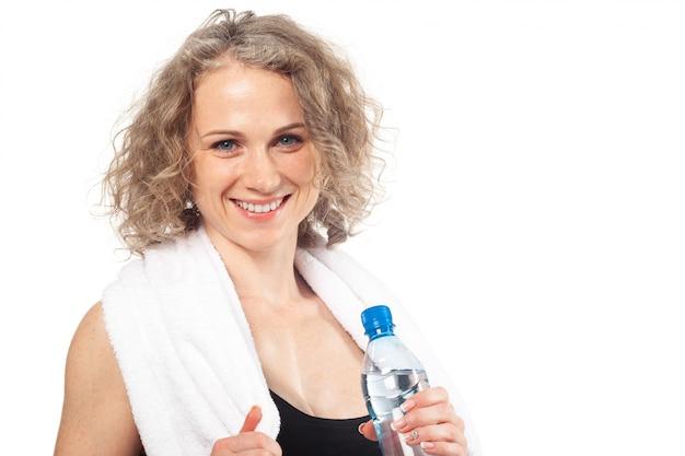 Ritratto di giovane donna sorridente felice nell'usura di forma fisica con la bottiglia di acqua Foto Premium
