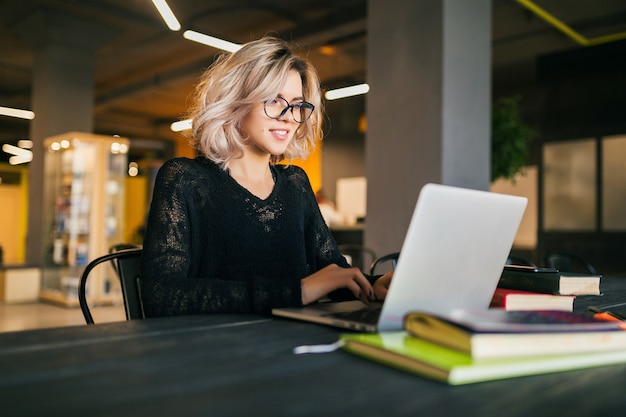 Ritratto di giovane donna sorridente graziosa che si siede al tavolo in camicia nera che lavora al computer portatile in ufficio di co-working, con gli occhiali Foto Gratuite