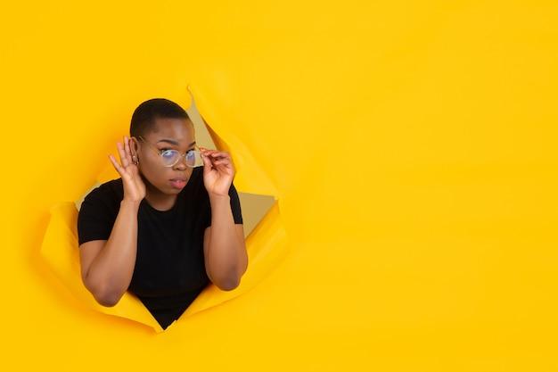 Ritratto di giovane donna su sfondo sfondato strappato giallo Foto Gratuite