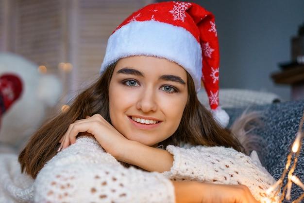Ritratto di giovane e bella donna con cappello di babbo natale su sfondo bokeh Foto Premium