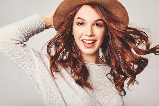 Ritratto di giovane elegante modello ridendo in abiti estivi casual grigi in cappello marrone con trucco naturale Foto Gratuite