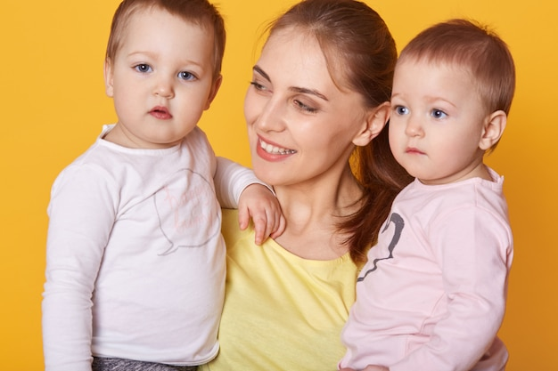 Ritratto di giovane madre che tiene i suoi piccoli gemelli Foto Gratuite