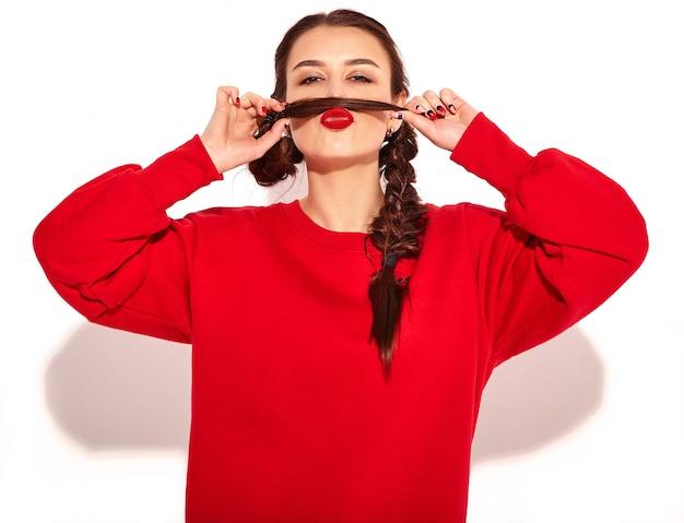 Ritratto di giovane modello di donna sorridente felice con trucco luminoso e labbra colorate con due trecce e occhiali da sole in abiti rossi estate isolati. fare baffi finti usando i propri capelli Foto Gratuite