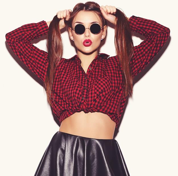 Ritratto di giovane modello felice della donna con trucco luminoso e le labbra variopinte in camicia a quadretti rossa ed occhiali da sole di estate isolati su bianco. impazzendo Foto Gratuite