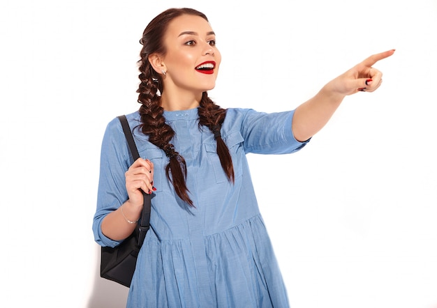 Ritratto di giovane modello sorridente felice della donna con trucco luminoso e labbra rosse con due trecce in mani in vestito blu variopinto da estate e zaino isolati. indicando il lato Foto Gratuite