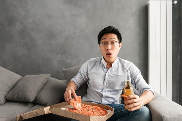 Ritratto di giovane pizza mangiatrice di uomini asiatica colpita Foto Premium