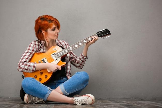 Ritratto di giovane ragazza con la chitarra su sfondo grigio. Foto Gratuite
