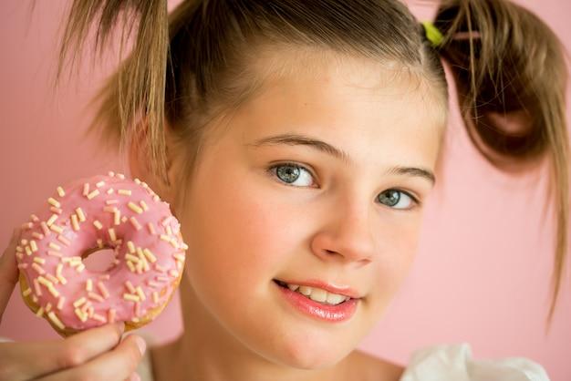 Ritratto di giovane ragazza guardando attraverso due ciambelle rosa Foto Premium