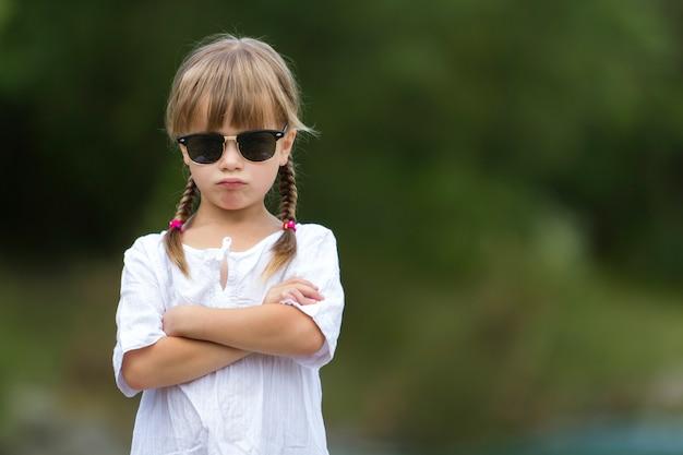 Ritratto di giovane ragazza prescolare bionda lunatica alla moda sicura abbastanza fredda fresca sveglia divertente con le trecce bionde in vestito bianco Foto Premium