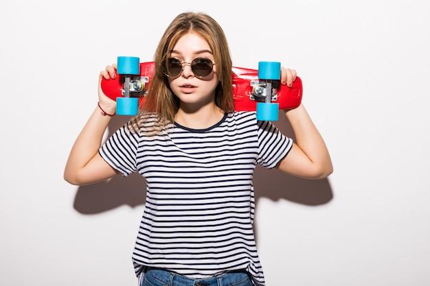 Ritratto di giovane ragazza teenager in occhiali da sole che posano con il pattino mentre controllando parete bianca Foto Gratuite