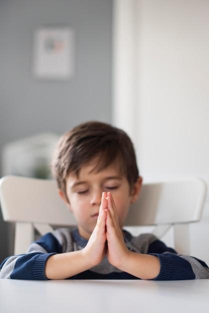 Ritratto di giovane ragazzo che prega a casa Foto Gratuite