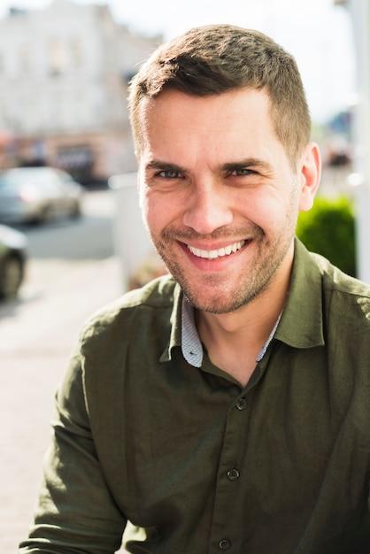 Ritratto di giovane sorridente che guarda l'obbiettivo Foto Gratuite