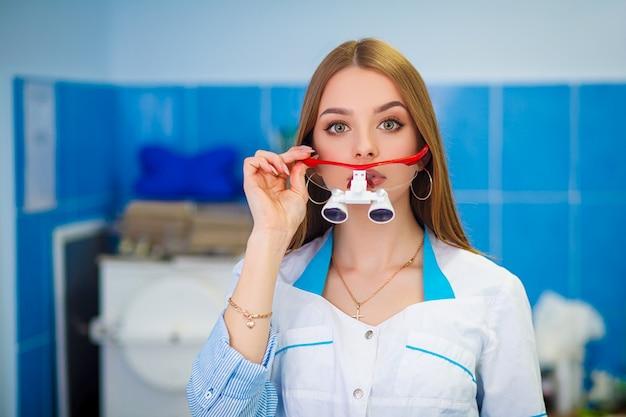 Ritratto di giovane stomatologo che fa fronte divertente mentre guardando macchina fotografica e sorridere. Foto Premium