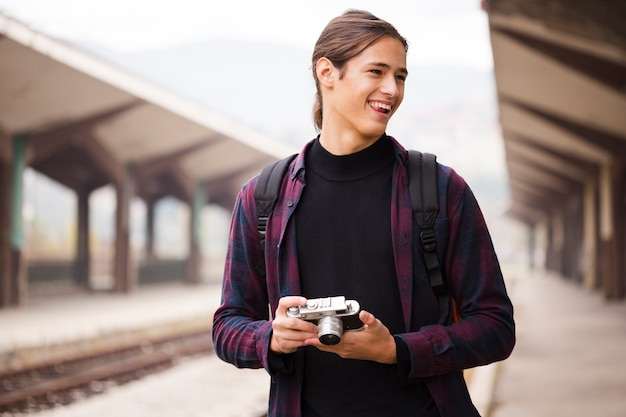 Ritratto di giovane turista che tiene una macchina fotografica Foto Gratuite