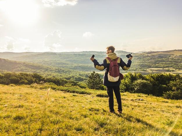 Ritratto di giovane uomo con attrezzatura fotografica e mani alzate camminando sul campo di montagna Foto Premium