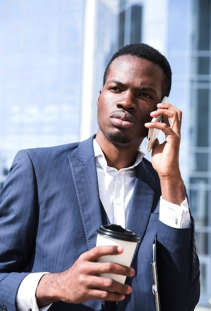 Ritratto di giovane uomo d'affari che parla sul telefono cellulare che tiene la tazza di caffè eliminabile Foto Gratuite