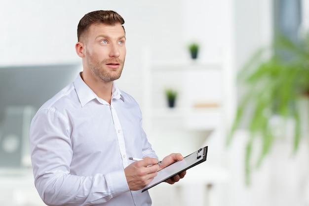 Ritratto di giovane uomo d'affari prendendo appunti Foto Premium