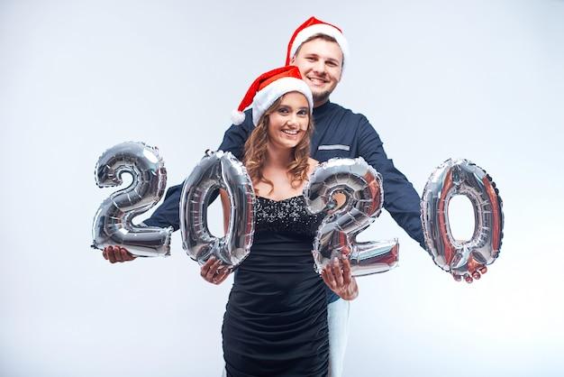 Ritratto di giovane uomo e donna felici in cappelli rossi di santa con i palloni metallici 2020. Foto Premium