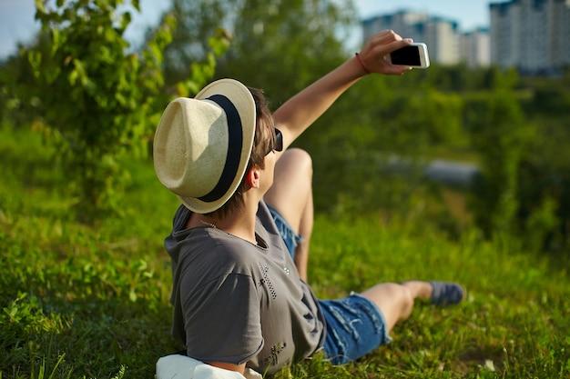 Ritratto di giovane uomo elegante moderno attraente in panno casual nel cappello con gli occhiali seduto nel parco in erba verde facendo selfie Foto Gratuite