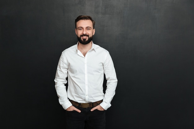 Ritratto di giovane uomo in camicia bianca in posa sulla fotocamera con ampio sorriso e le mani in tasca su grigio scuro Foto Gratuite
