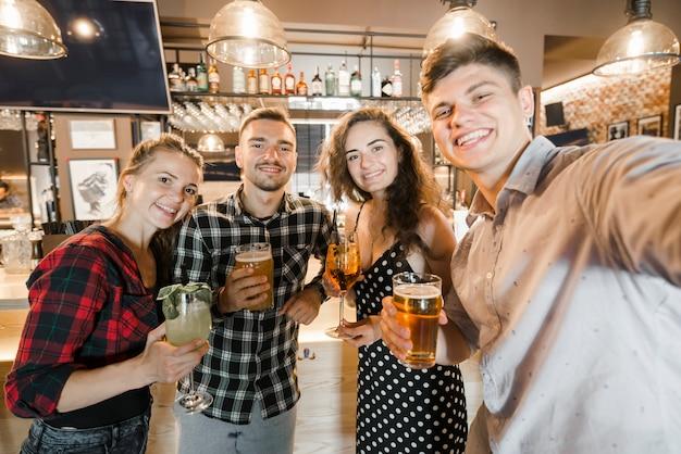 Ritratto di giovani amici in possesso di bicchieri di bevande al bar Foto Gratuite