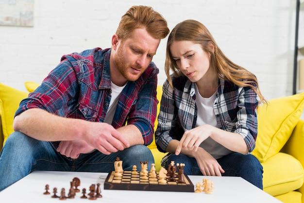 Ritratto di giovani coppie che giocano insieme gli scacchi di legno a casa Foto Gratuite